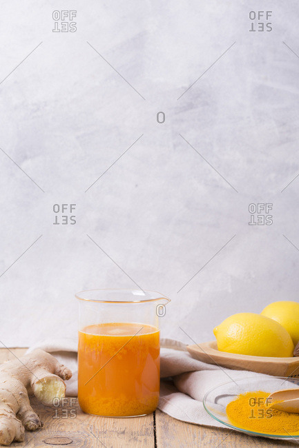 Beaker filled with orange and lemon juice with turmeric and ginger in front of light background