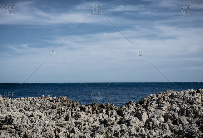 A sailing ship on the horizon of the Mediterranean Sea with a rocky coastline on the d'Azur near Antibes in France.