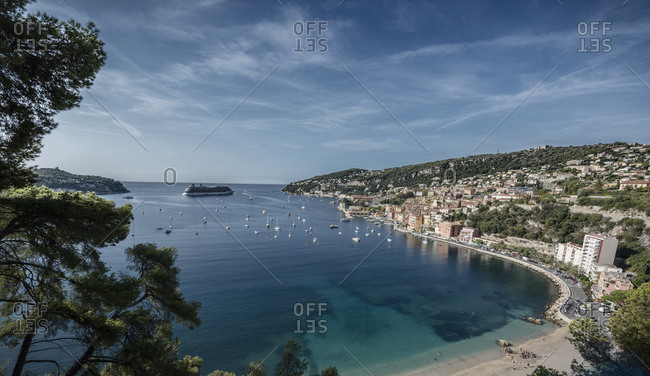 A cruise ship and sailing boats in the bay of Villefranche-sur-Mer on the d'Azur in France.