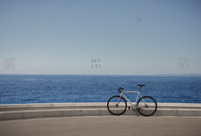 The waters of the Mediterranean sea and a bike resting on the promenade in the city of Nice on the d'Azur in France.