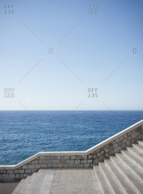 The waters of the Mediterranean sea and the promenade with stairs in the city of Nice on the d'Azur in France.