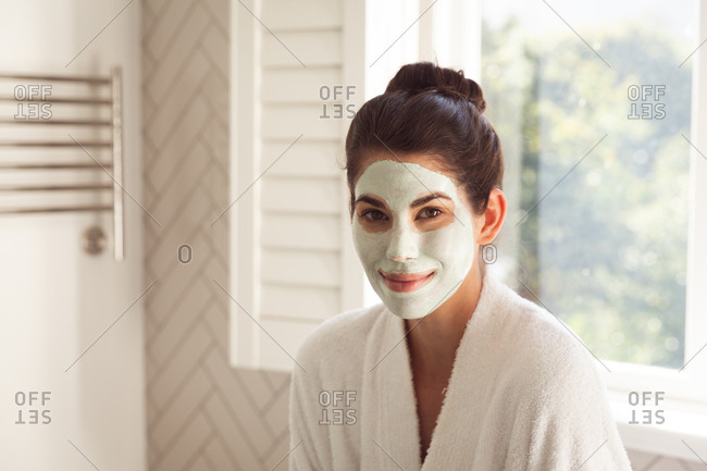 Portrait of mixed race woman spending time at home, with face mask on in bathroom. Self isolating and social distancing in quarantine lockdown during coronavirus covid 19 epidemic.