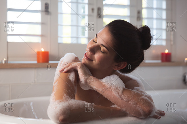 Mixed race woman spending time at home, lying in bathtub relaxing with eyes closed in bathroom. Self isolating and social distancing in quarantine lockdown during coronavirus covid 19 epidemic.