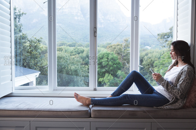 Mixed race woman spending time at home, sitting on window seat holding smartphone in sitting room. Self isolating and social distancing in quarantine lockdown during coronavirus covid 19 epidemic.
