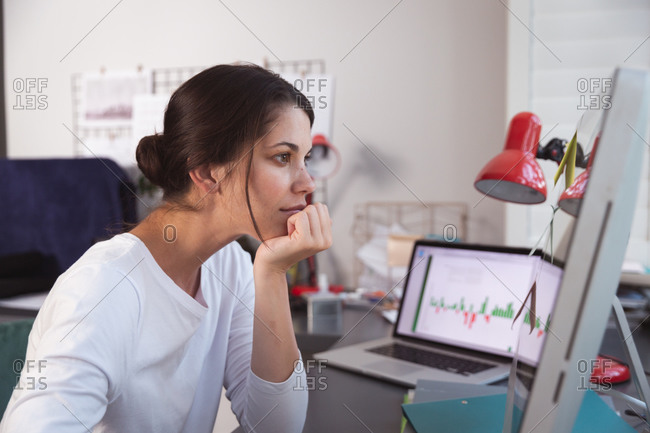 Mixed race woman spending time at home, sitting at desk, using computer, working from home. Self isolating and social distancing in quarantine lockdown during coronavirus covid 19 epidemic.
