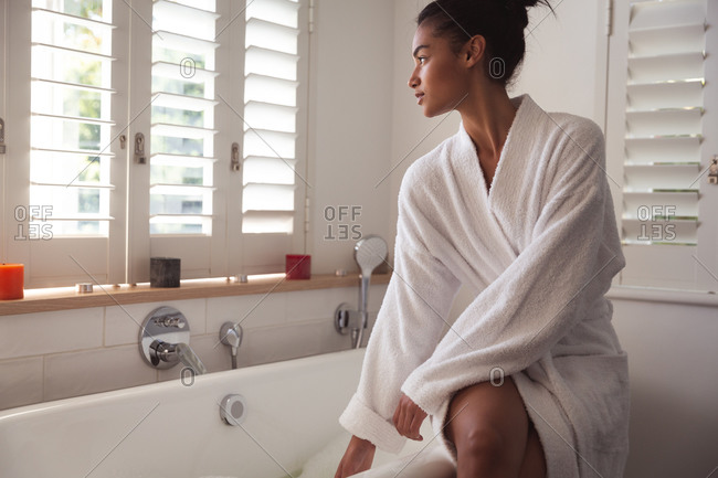Mixed race woman spending time at home, sitting on bathtub running bath in bathroom. Self isolating and social distancing in quarantine lockdown during coronavirus covid 19 epidemic.