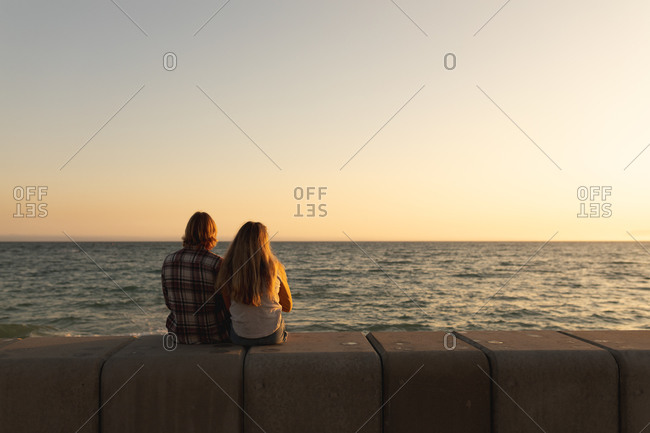 Rear view of Caucasian couple sitting together on a promenade by the sea at sunset, looking out to sea. Romantic beach holiday couple