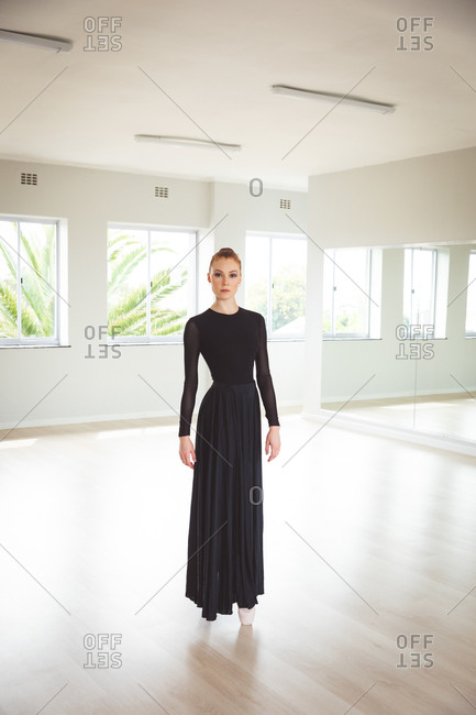 Portrait of an attractive Caucasian female ballet dancer with red hair in a bun wearing a long, black dress, standing on her toes in pointe shoes in a bright ballet studio, looking straight to camera