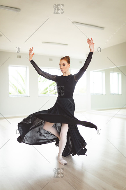 Attractive Caucasian female ballet dancer with red hair dancing wearing a long, black, dress, practicing ballet in a bright studio, focusing on her exercise.