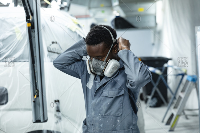 African American male mechanic wearing overalls working in a township car workshop, putting his breathing mask on before spray painting a car