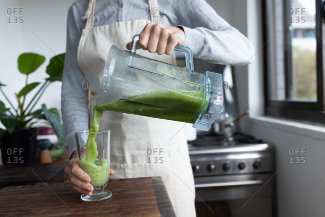 Mid section of a Caucasian woman spending time at home, pouring smoothie. Lifestyle at home isolating, social distancing in quarantine lockdown during coronavirus covid 19 pandemic.