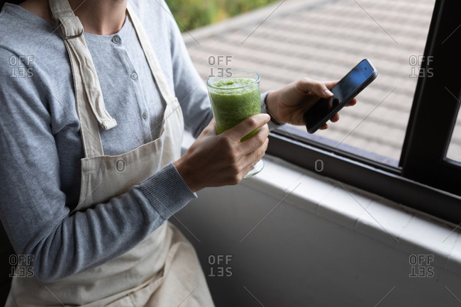 Mid section of a Caucasian woman spending time at home, drinking smoothie, using her smartphone. Lifestyle at home isolating, social distancing in quarantine lockdown during coronavirus covid 19 pandemic