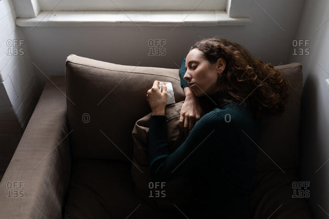 Mid section of a Caucasian woman spending time at home, lying on the couch with a tissue. Lifestyle at home isolating, social distancing in quarantine lockdown during coronavirus covid 19 pandemic.