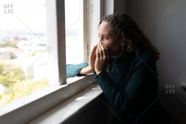A Caucasian woman spending time at home, blowing her nose. Lifestyle at home isolating, social distancing in quarantine lockdown during coronavirus covid 19 pandemic.