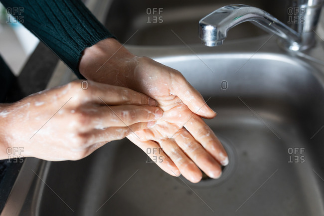 Hands of a Caucasian woman spending time at home, washing her hands. Lifestyle at home isolating, social distancing in quarantine lockdown during coronavirus covid 19 pandemic.
