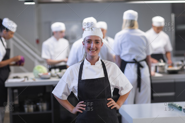 Portrait of a happy Caucasian female chef looking at the camera and smiling hands on hips, with other chefs cooking in the background. Cookery class at a restaurant kitchen. Workshop cooking food.