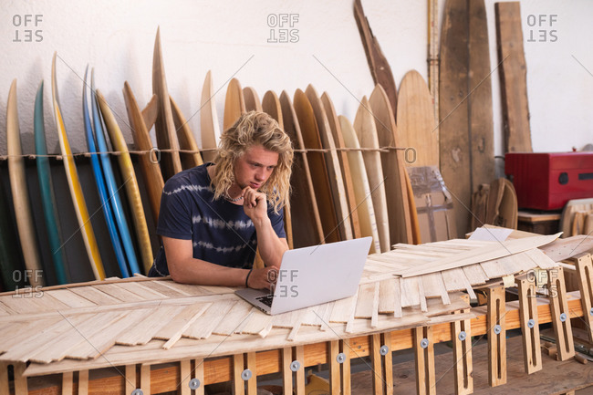 Caucasian male surfboard maker in his studio, working on a project using his laptop, with surfboards in a rack in the background. Small business sports technology on line.