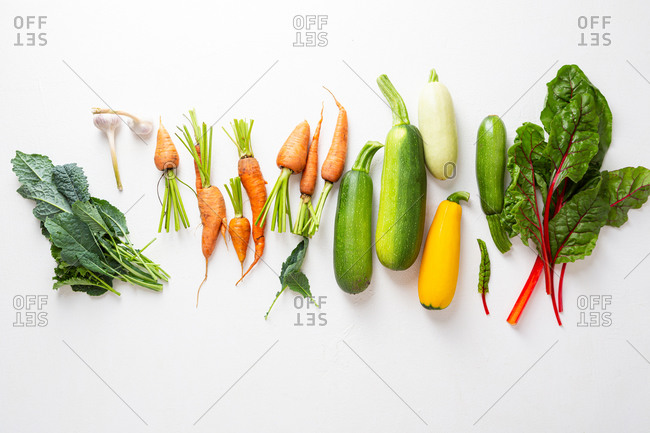 Overhead view of fresh summer produce on white surface
