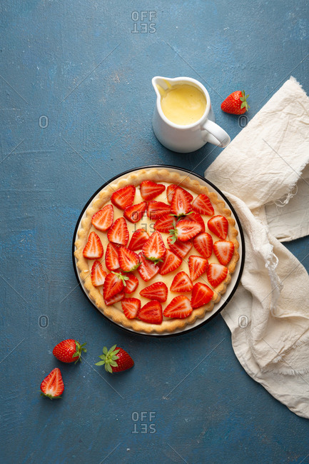 Strawberry pie with custard on blue background