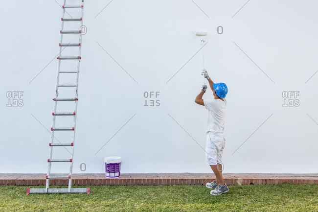 Rear view of painter rolling white paint on the outside of a building