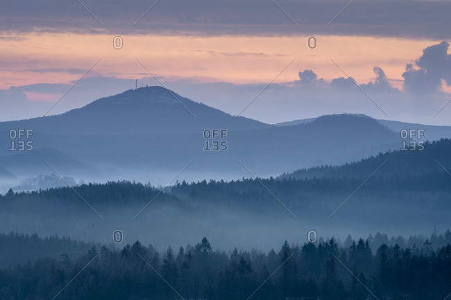 Plesivec hill and Jedlova mountain in Lusatian mountains rising above fog taken from Krizovy vrch hill at sunrise