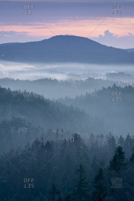 Plesivec hill in Lusatian mountains rising above fog taken at sunrise
