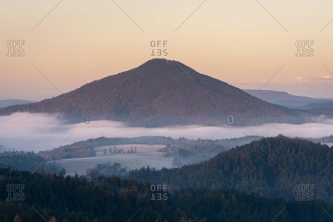 Ruzovsky vrch hill rising above fog at sunrise