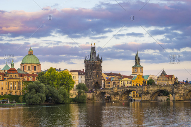 June 13, 2017: Charles Bridge and Church of Saint Francis of Assisi with Old Town Bridge Tower against sky at sunset, Prague, Bohemia, Czech Republic
