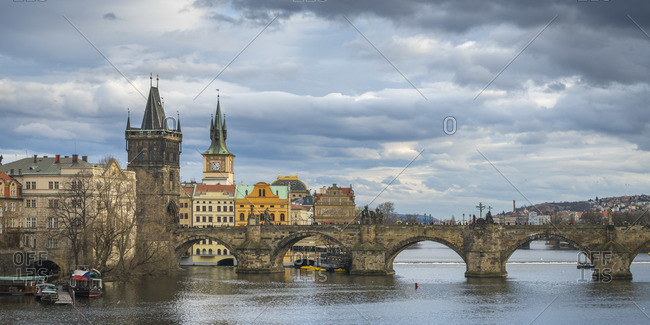 March 13, 2018: Charles Bridge and Old Town Bridge Tower against cloudy sky, Prague, Bohemia, Czech Republic