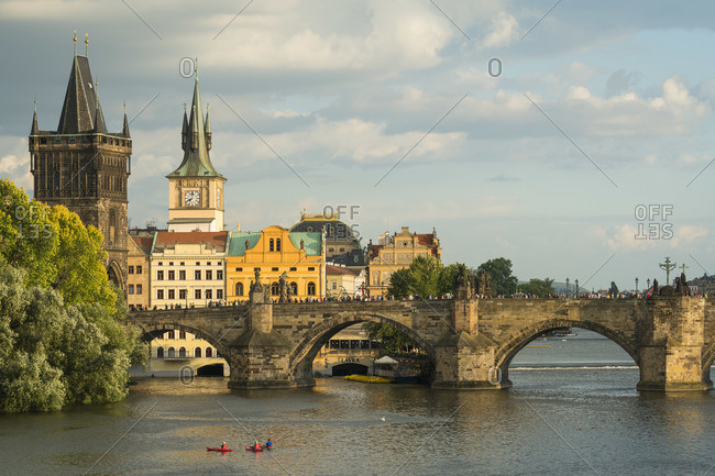 June 26, 2018: Three kayakers admiring Charles Bridge on Vltava River, Prague, Bohemia, Czech Republic