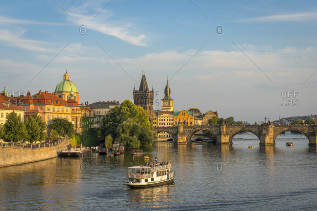 July 17, 2019: Boat going towards Charles Bridge and Old Town Bridge Tower, Prague, Bohemia, Czech Republic