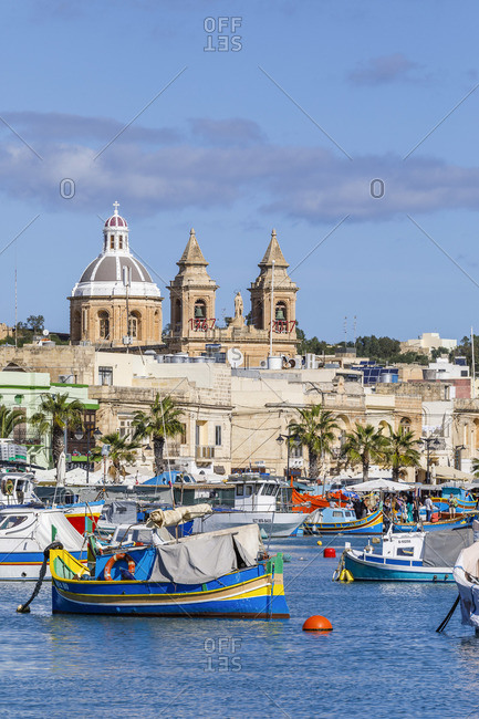 October 29, 2017: Marsaxlokk, Malta, famous for its colorful fishing boats called Iuzzu, in the background the Parish church dedicated to Our Lady of Pompeii