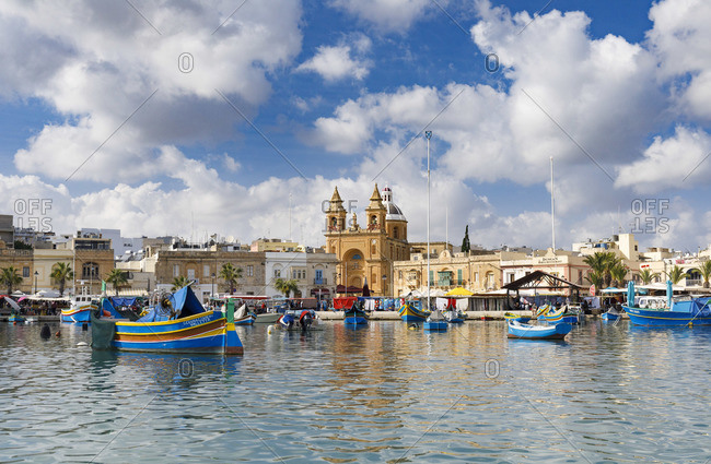 October 29, 2017: Marsaxlokk, Malta, famous for its colorful fishing boats called Iuzzu, in the background the Parish church dedicated to Our Lady of Pompeii, Malta