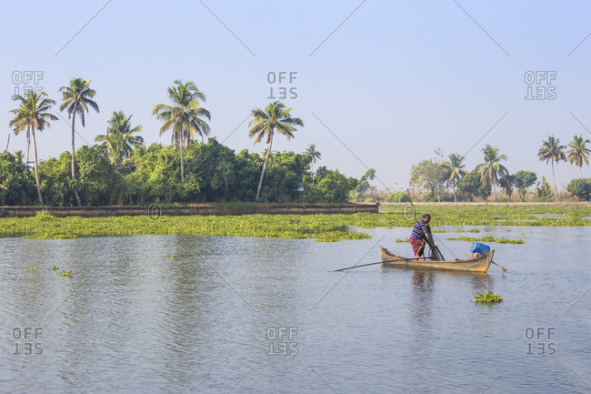 February 5, 2020: India, Kerala, Alappuzha (Alleppey),  Alappuzha (Alleppey) backwaters, Man fishing from dugout canoe