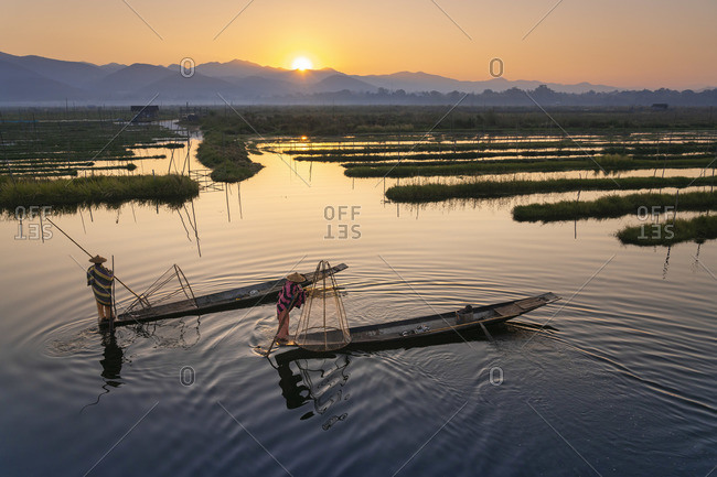 February 14, 2020: Two fishermen catching fish from boats using traditional conical nets at sunrise, Floating Gardens, Lake Inle, Nyaungshwe Township, Taunggyi District, Shan State, Myanmar