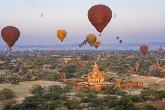 February 12, 2020: Old temple in Bagan and hot-air balloons before sunrise, UNESCO, Old Bagan, Mandalay Region, Myanmar