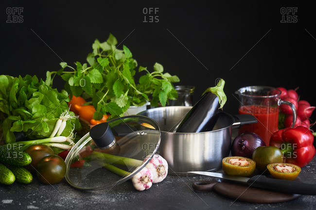 Fresh vegetables and pot in front of dark background