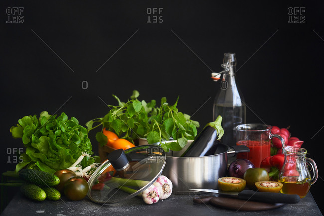 Variety of vegetables and pot in front of dark background