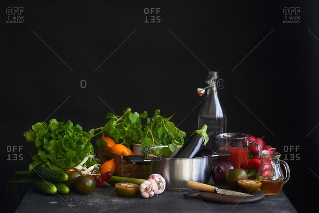 Various fresh vegetables and pot in front of dark background