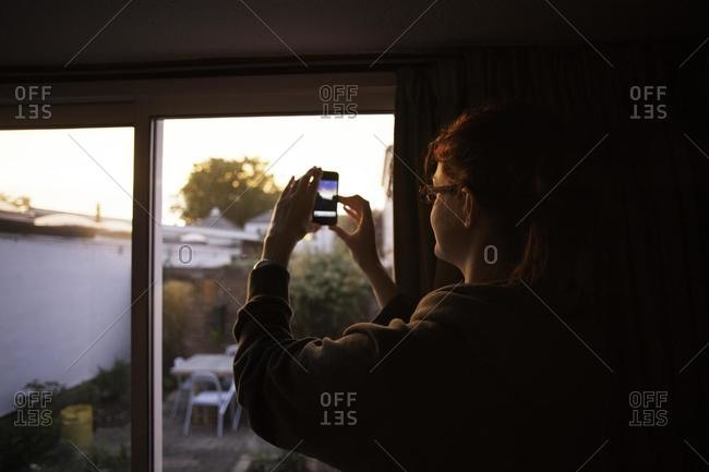 Woman standing in a living room Taking a photo With her mobile phone