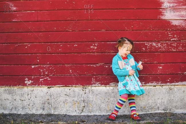 Happy girl standing by a red wall holding a feather, USA