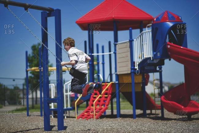 Boy sitting on a swing in a playground, Orangeville, Ontario, Canada