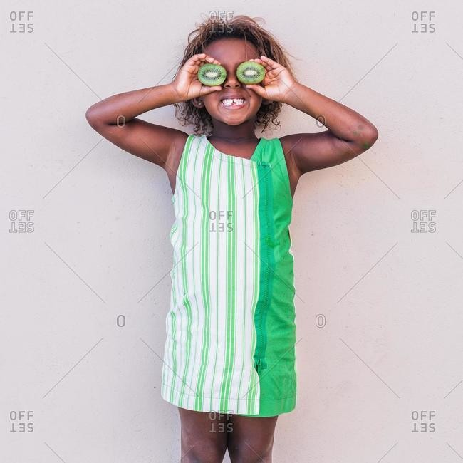 Smiling girl in green dress holding kiwi fruit in front of her eyes
