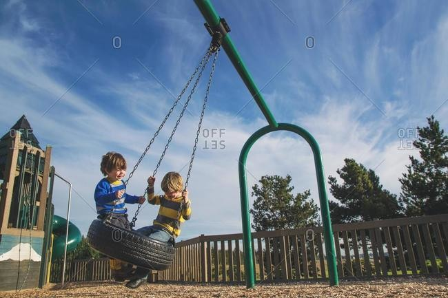 Two young boys swinging on a tire swing at a park