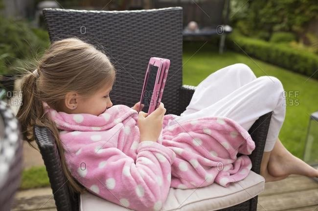 Girl sitting in the garden watching a film on a digital tablet