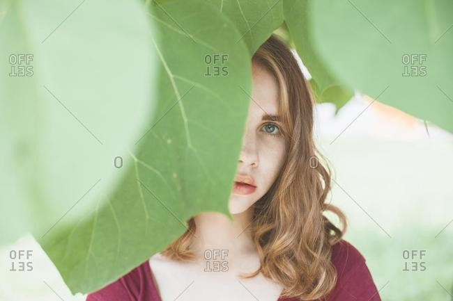 Portrait of a young woman with face obscured by leaves