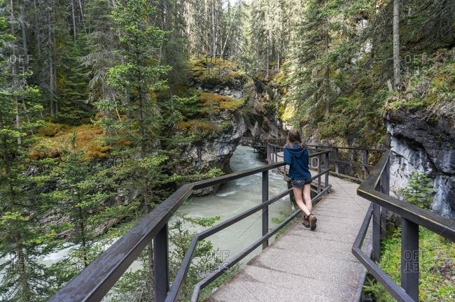 Teenage Girl standing on walkway, Johnston Canyon, Banff National Park, Alberta, Canada