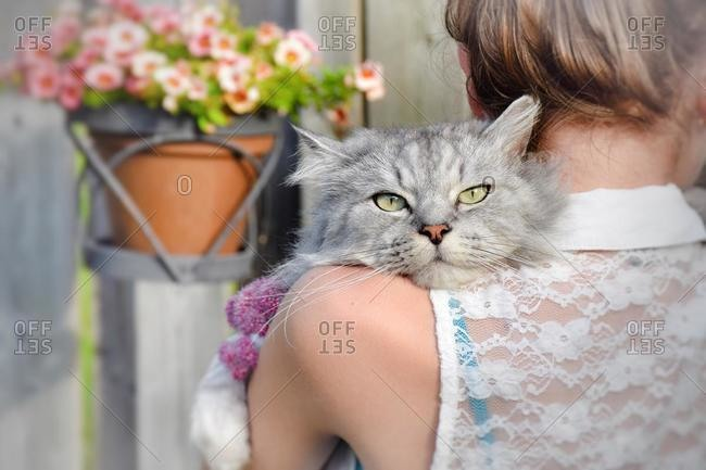 Rear view of a teenage girl holding a cat over her shoulder