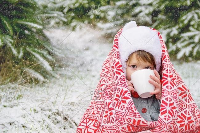 Girl wrapped in a blanket drinking hot cocoa in the snow