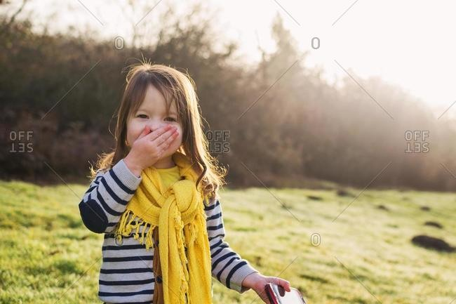 Laughing girl with hand in front of her mouth, holding mobile phone